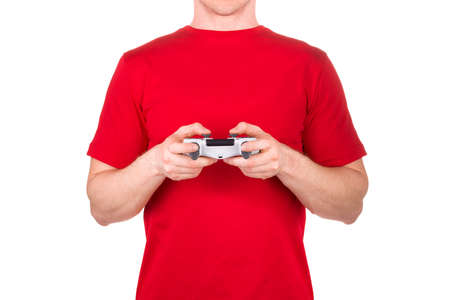 Man in red t-shirt holding gamepad and playing video games isolated white background  . Concept of t shirt template or gaming