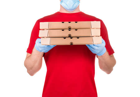 Delivery man in red t-shirt and blue medical gloves holding pizza boxes isolated white background  . Concept of safety delivery in virus or coronavirus quarantine