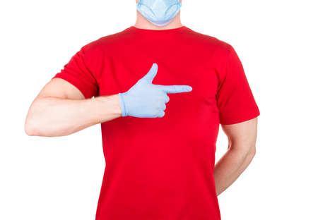 Man in red t-shirt and blue face mask and gloves pointing finger on the side isolated white background . Concept of t shirt template or delivery
