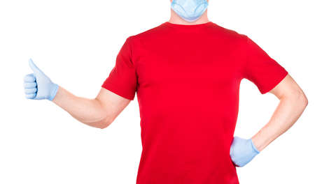 Man in red t-shirt and blue face mask and gloves showing thumbs up gesture isolated white background  . Concept of t shirt template and mock-up for print