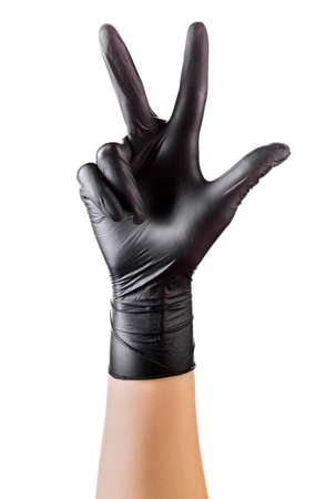 Hand in black gloves showing 3 fingers and counting isolated on black background.