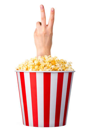 Female hand sticks out of a bucket with popcorn isolated on white background.