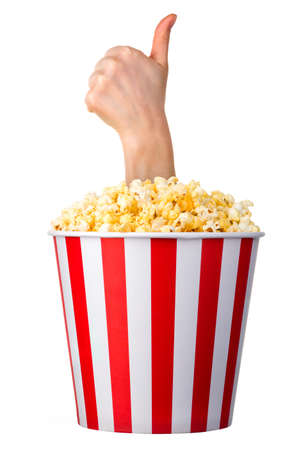Female hand sticks out of a bucket with popcorn in gesture of like sign, giving thumb up isolated on white background.