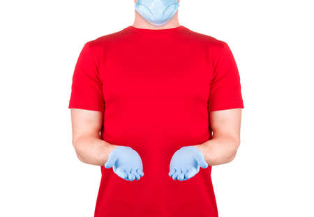 Man in red t-shirt in disposable face mask holding something on his palm isolated white background  . Concept of t shirt template or delivery 版權商用圖片