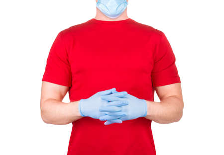 Man in red t-shirt with blue face mask and gloves praying to god and asking for forgiveness or miracle isolated white background  . Concept of t shirt template and mock-up for print 版權商用圖片