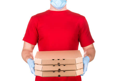 Delivery man in red t-shirt and blue medical gloves holding pizza boxes isolated white background with clipping path. Concept of safety delivery in virus or coronavirus quarantine