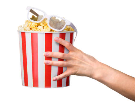 Woman hand holding striped bucket with popcorn and 3D glasses isolated on white background. Isolated with clipping path.