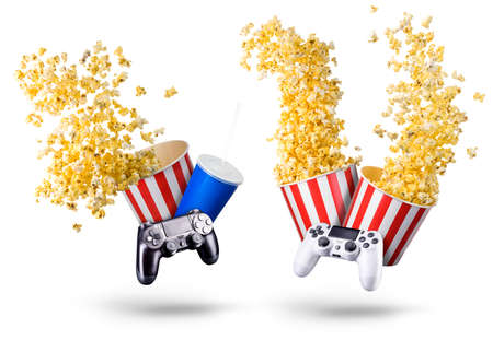 Paper striped bucket with popcorn, cup of soft drink and video game joystick isolated on white background, movie night concept or watching TV.