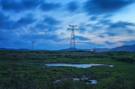 A small swamp with high voltage electric towers on the grassland in the evening Stockfoto