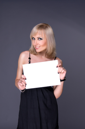 blonde holding itself in hands of white sheet of paper photo