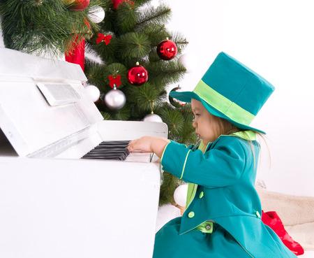 girl in costume leprechaun playing the piano photo
