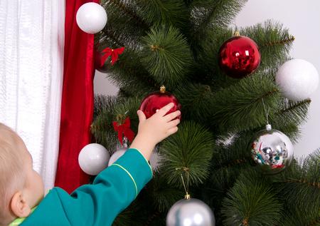 decorates: child decorates a Christmas tree New Year balls Stock Photo