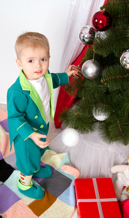 child decorates a Christmas tree New Year balls photo