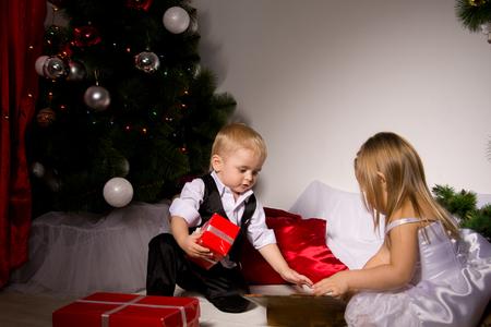 uitpakken: Kinderen uitpakken cadeautjes onder de kerstboom New Year's Eve