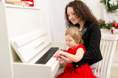 mother and daughter playing on white piano in bright room photo