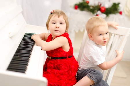 boy and girl playing on white piano in bright room photo