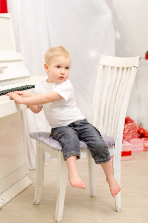boy sitting near white piano in bright room photo