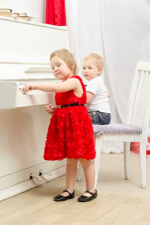 boy with girl sitting near white piano in bright room photo