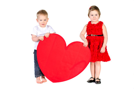 Children with huge heart made ​​of red paper isolated on white background photo
