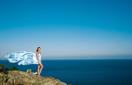 red-haired girl in a blue dress and flying. against the sky and the sea photo
