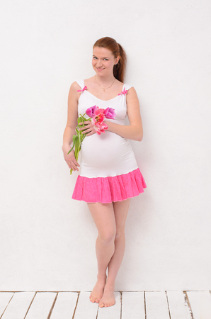 pregnant holding a bouquet of tulips. Stands near a white wall photo