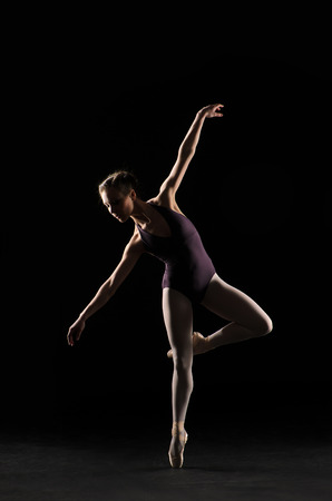 Silhouette ballet dancer in black swimsuit at the studio background photo