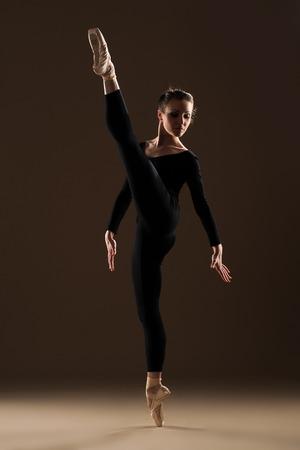 ballet dancer in jump on beige  photo