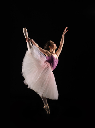 ballet dancer in jump on black