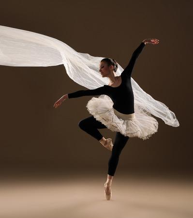ベージュ色の背景上のジャンプのバレエ ダンサー 写真素材