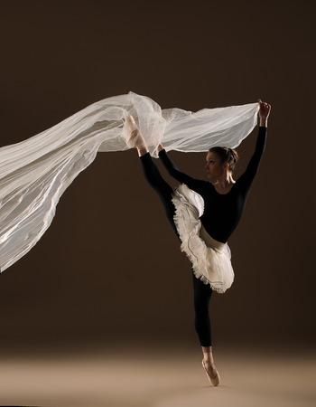 ballet dancer in jump on beige background photo