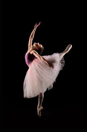 黒い背景にジャンプのバレエ ダンサー