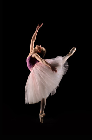 ballet dancer in jump on black background