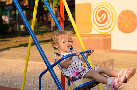 totter: little curly girl riding on swings Stock Photo