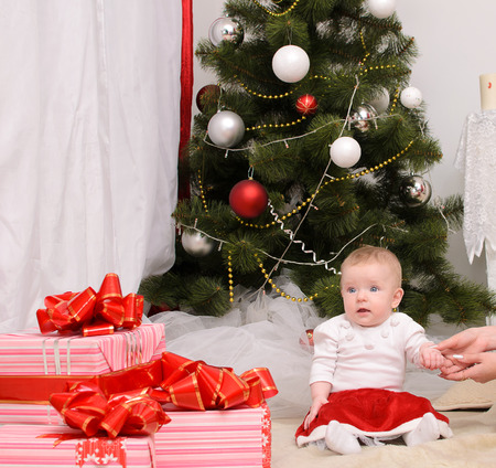 Christmas baby in interior of  room, sitting near Christmas tree photo