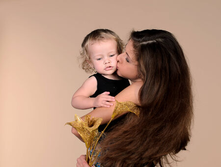 mother holding baby on beige background photo