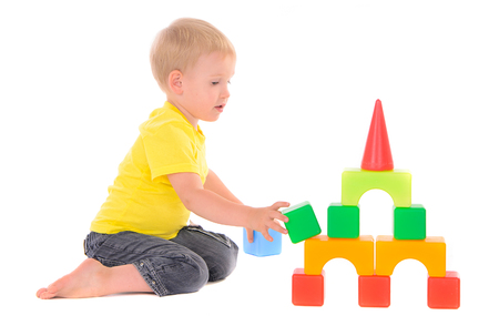 builds: boy builds a building of colored cubes Stock Photo