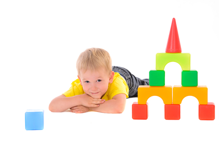 boy lying near toy building of colored cubes photo