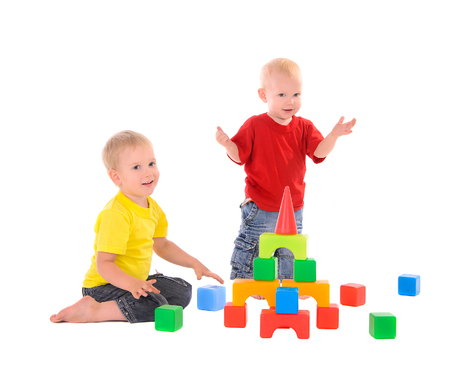 two brothers builds a building of colored cubes photo