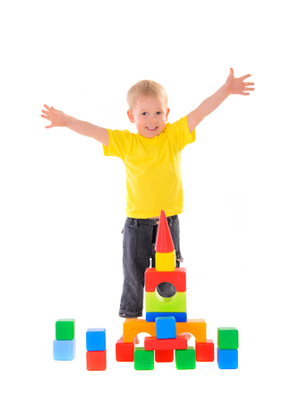 child builds a building of colored cubes photo