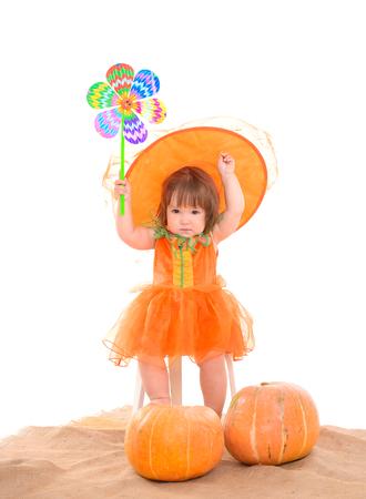little girl in orange costume with pumpkins photo