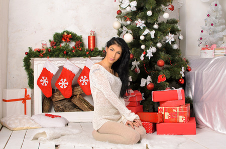 young graceful brunette woman in christmas interior in white and red photo
