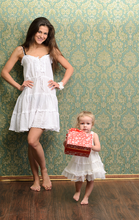 young mommy and little daughter with gift in family style photo