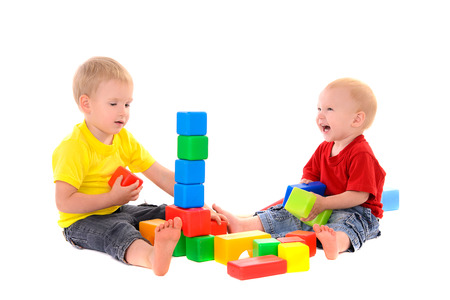 two brothers build toy building of colored cubes on white background photo