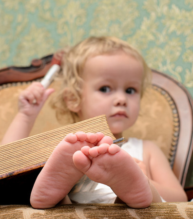 toes: little girl with book in armchair in retro style