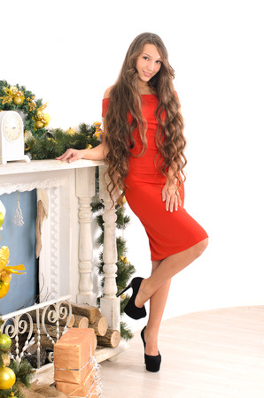 long red hair woman: attractive young lady with long curly hair in red gown in christmas interior Stock Photo
