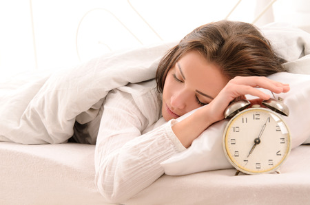 gente durmiendo: pronto a despertar para dormir atractiva mujer joven con reloj despertador