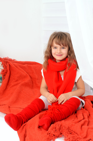 red scarf: beautiful girl in red scarf on white wall