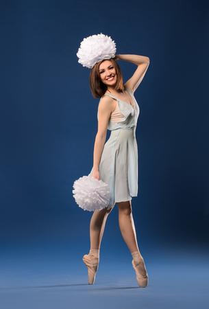female dancer cheerleader on tiptoe with pompons on dark blue studio background photo