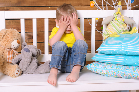 eyes closing: Boy sitting on bench and closing his eyes with hands indoors
