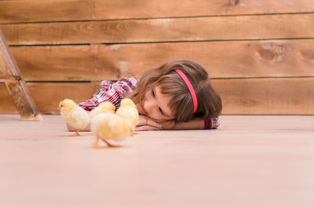 downy: Little girl lying on floor and watching for downy chickens Stock Photo